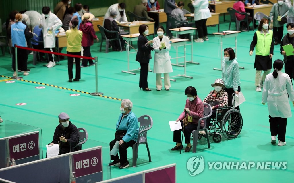 Senior citizens wait in line to see doctors before getting vaccinated at a gymnasium in Gwangju on April 19, 2021. (Yonhap)
