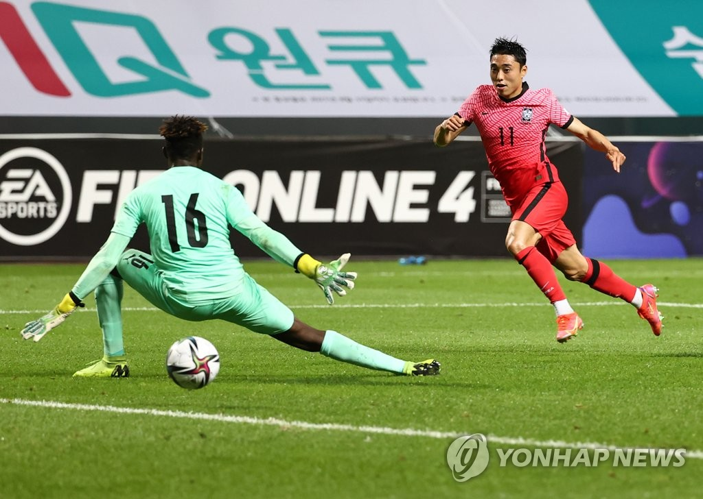 Lee Dong-jun (R) of the South Korean men's Olympic football team scores past Ghana goalkeeper William Emmanuel Essu during a friendly match at Jeju World Cup Stadium in Seogwipo, Jeju Island, on June 15, 2021. (Yonhap)