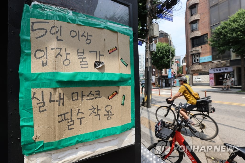 This photo taken on June 20, 2021, shows a sign posted near the entrance of a bar in Seoul to inform customers that private gatherings of five or more people are not allowed under the current social distancing rules amid the coronavirus pandemic. (Yonhap)
