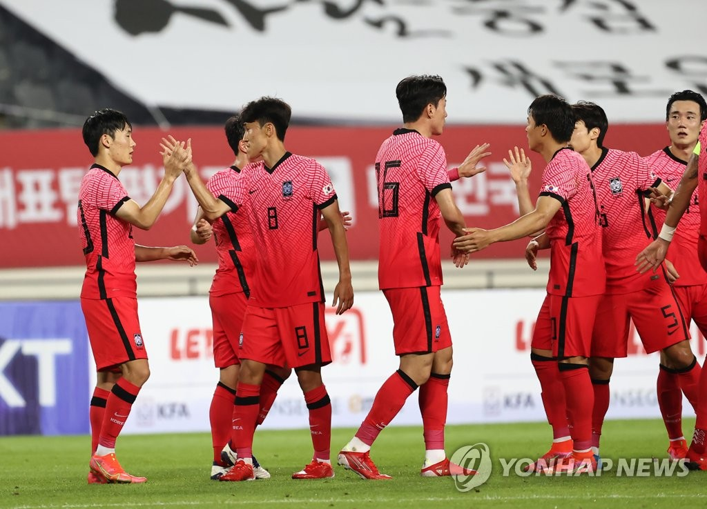 South Korean players exchange high-fives after a 2-2 draw against Argentina in the teams' Olympic men's football tuneup match at Yongin Mireu Stadium in Yongin, 50 kilometers south of Seoul, on July 13, 2021. (Yonhap)