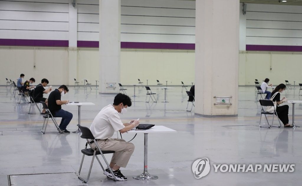 Visitors at the Coffee Expo Seoul 2021 take self-virus tests before entering the venue in southern Seoul on July 14, 2021. (Yonhap)