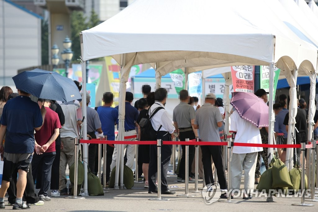 People stand in line to take COVID-19 tests at a screening station in front of Seoul Station on July 23, 2021. (Yonhap)