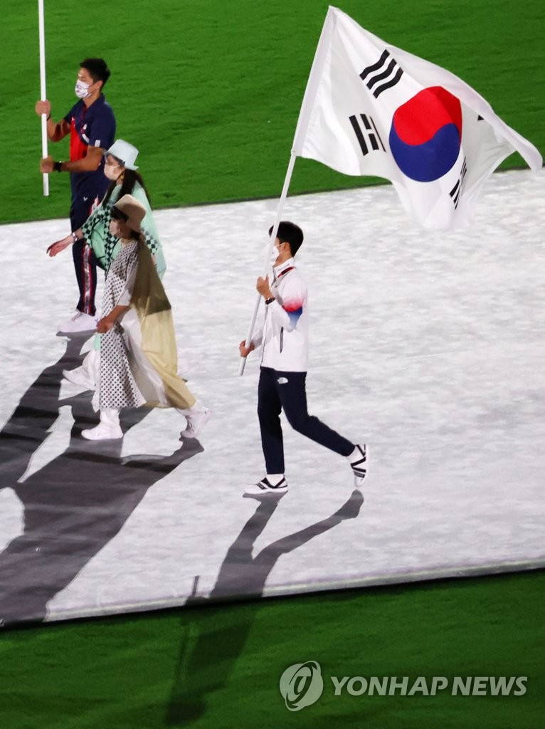 """South Korean modern pentathlon bronze medalist Jun Woong-tae carries the national flag, """"Taegeukgi,"""" during the closing ceremony of the Tokyo Olympics at the National Stadium in Tokyo on Aug. 8, 2021. (Yonhap)"""