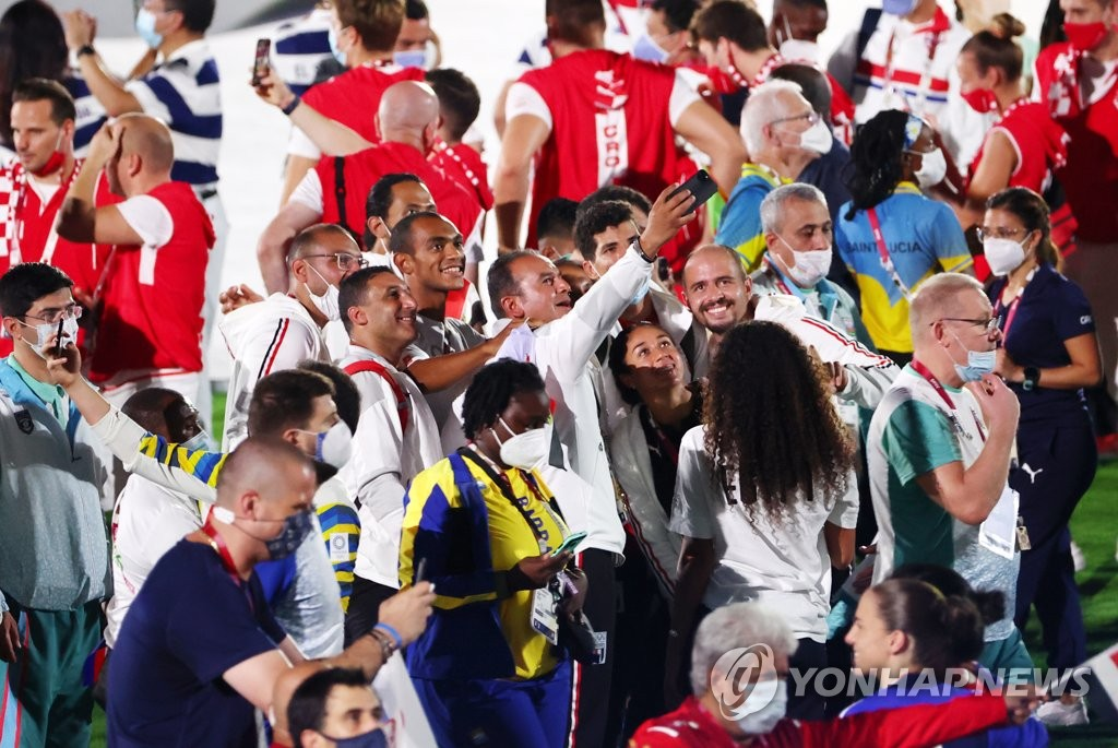 Unmasked athletes and officials take a selfie during the closing ceremony of the Tokyo Olympics at the National Stadium in Tokyo on Aug. 8, 2021. (Yonhap)