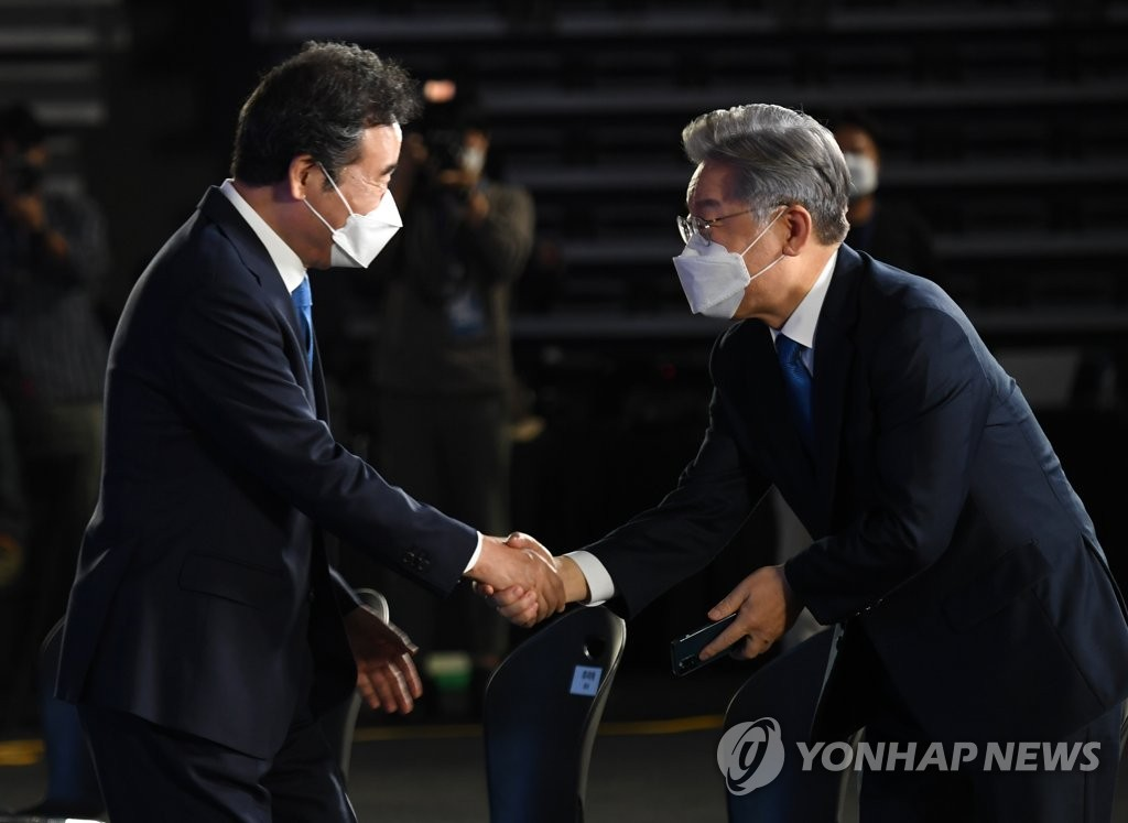 Gyeonggi Gov. Lee Jae-myung (R) and ex-Prime Minister Lee Nak-yon shake hands at a party convention in Seoul on Oct. 10, 2021, which was held to pick the ruling Democratic Party's candidate for the 2022 presidential election. (Pool photo) (Yonhap)